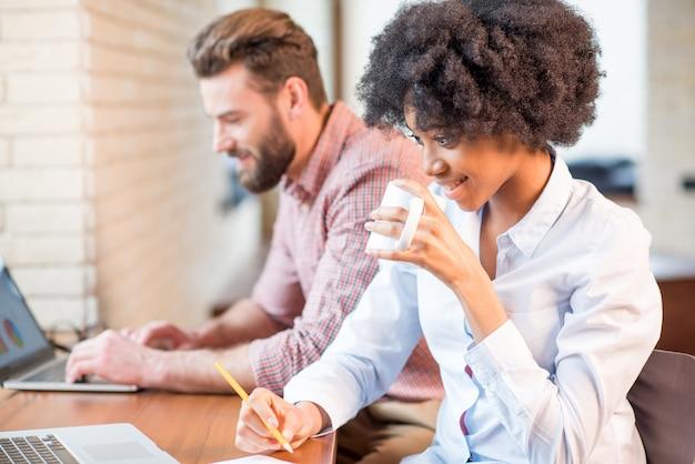 Bella donna d'affari africana e uomo caucasico che lavorano insieme a computer portatili e tazze di caffè vicino alla finestra del bar o dell'ufficio
