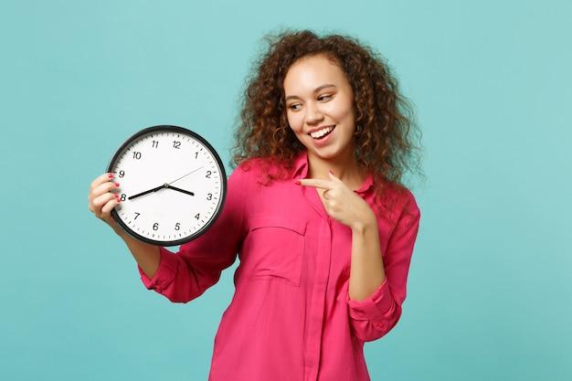 Bella ragazza africana in abiti casual rosa che punta il dito indice sull'orologio rotondo isolato sul fondo della parete turchese blu in studio. persone sincere emozioni, concetto di stile di vita. mock up copia spazio.