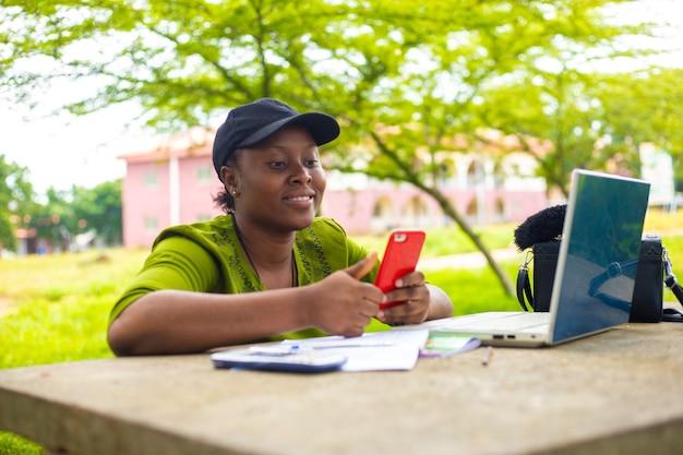 Bello studente africano studente universitario che utilizza il computer portatile all'aperto