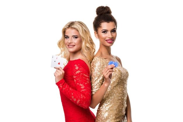 Bella donna africana e giovane donna caucasica con lunghi capelli biondi chiari in abito da sera. tenendo carte da gioco e fiches. isolato. poker
