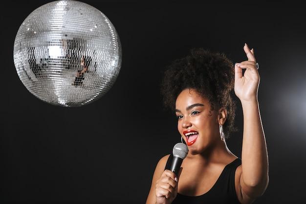 Bella donna africana in piedi con la palla da discoteca d'argento isolato su uno spazio nero, tenendo il microfono