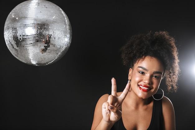 Bella donna africana in piedi con la palla da discoteca d'argento isolato su uno spazio nero