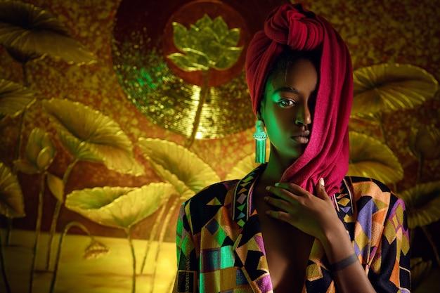 Bella donna africana che indossa una sciarpa luminosa sulla sua testa