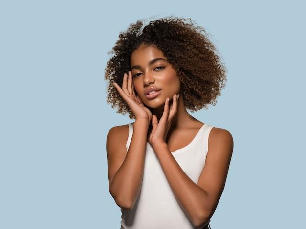 Bella donna africana bianca t-shirt ritratto taglio di capelli afro che tocca il suo viso colore di sfondo blu