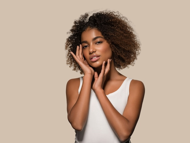 Bella donna africana bianca t-shirt ritratto taglio di capelli afro che tocca il suo viso colore di sfondo marrone