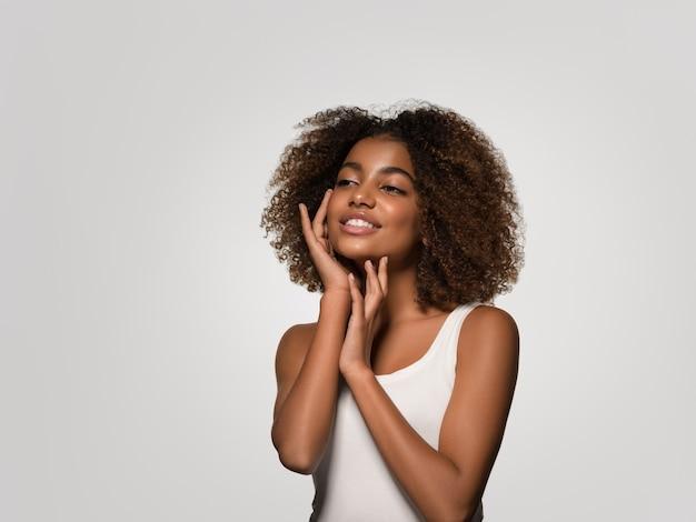 Bella donna africana bianca t-shirt ritratto taglio di capelli afro che tocca il suo viso colore di sfondo grigio
