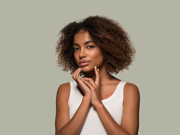 Bella donna africana bianca t-shirt ritratto taglio di capelli afro che tocca il suo viso colore di sfondo verde