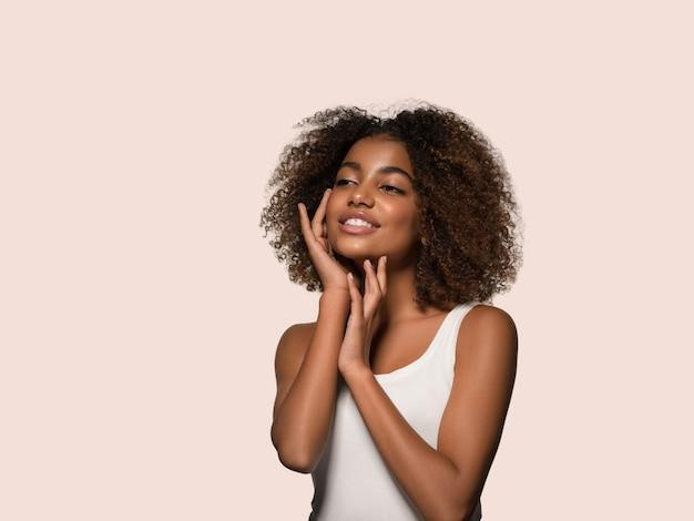 Bella donna africana bianca t-shirt ritratto taglio di capelli afro che tocca il suo viso colore di sfondo rosa