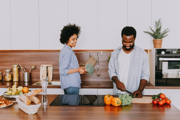 Bella coppia afroamericana che cucina a casa - bella e allegra coppia nera che prepara la cena insieme in cucina