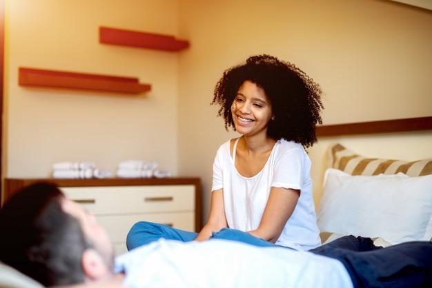 Bella donna afroamericana che esamina ragazzo sul letto.