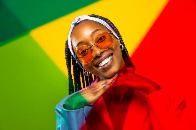 Bella donna afroamericana con acconciatura afro e vestiti alla moda - ritratto di giovane ragazza nera in studio