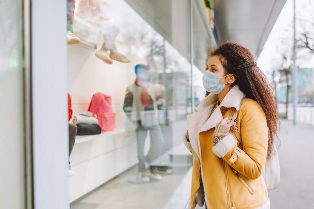 Bella donna dai capelli afro che indossa la maschera protettiva medica stare sulla strada della città e guardare la finestra del negozio.