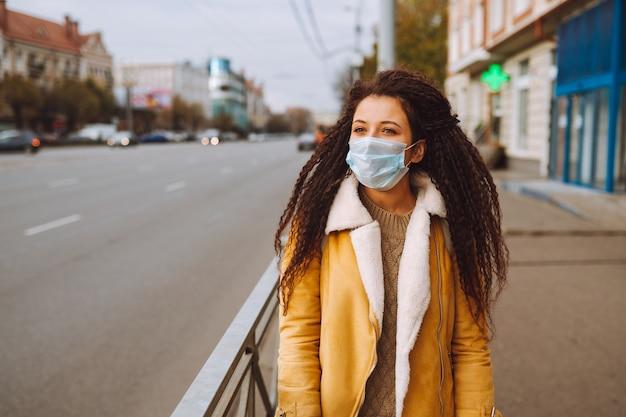 Bella donna dai capelli afro che indossa la maschera protettiva medica stare sulla strada della città.