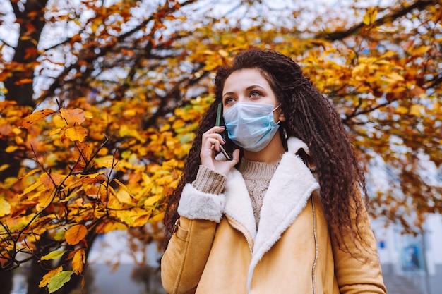 Bella donna dai capelli afro che indossa la maschera protettiva medica stare sulla strada e parlare per telefono.