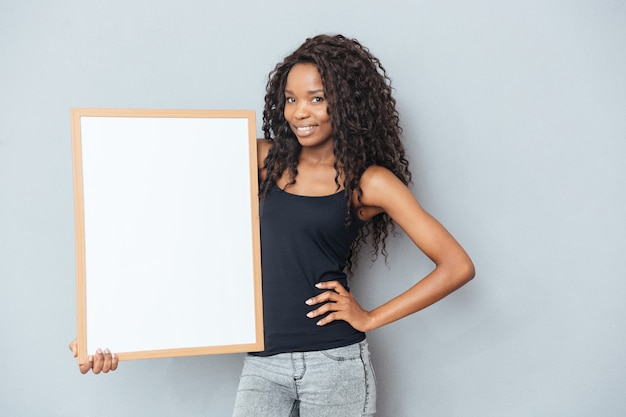 Bella donna afro che mostra bordo bianco su muro grigio gray