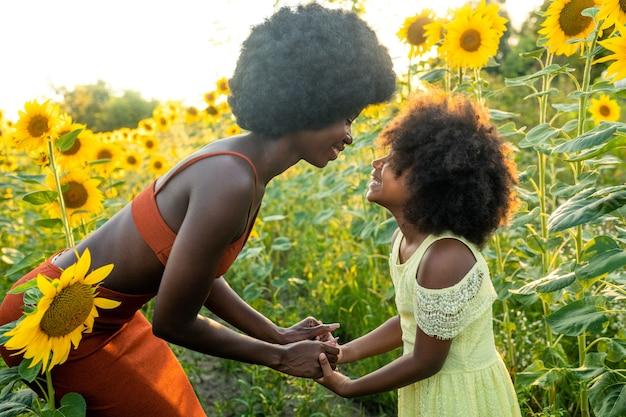 Bella mamma e figlia afroamericane che giocano e si divertono in un campo di girasoli