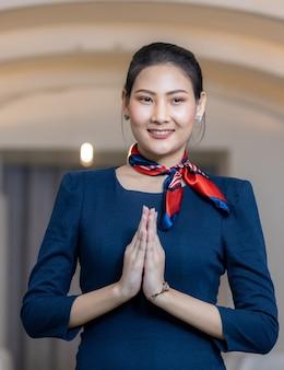 Bella hostess in un aereo sorridente, ritratto di hostess asiatica in posa sawasdee, equipaggio di cabina o hostess che lavora in aereo.