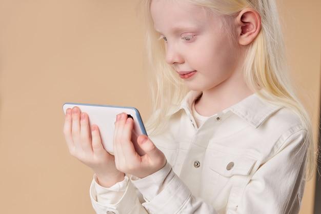 Bello bambino albino che tiene smartphone bianco nelle mani isolate