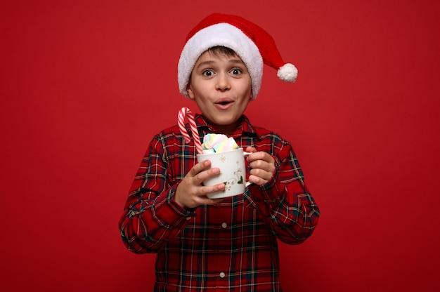 Bellissimo ragazzo preadolescente stupito che indossa un cappello da babbo natale posa su sfondo rosso con una tazza di cioccolata calda con marshmallow e zucchero filato dolce a strisce. concetto di natale con copia spazio per annuncio