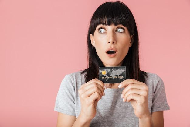 Una bella donna felice eccitata incredibile in posa isolata sul muro rosa chiaro muro in possesso di carta di credito.