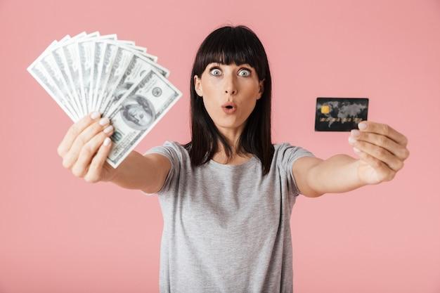 Una bella donna felice eccitata incredibile in posa isolata sopra la parete rosa chiaro della parete che tiene soldi e carta di credito.