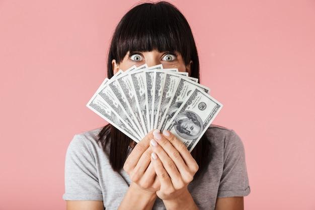 Una bella donna felice emozionante stupefacente che posa isolata sopra la parete rosa chiaro del muro che tiene i soldi.