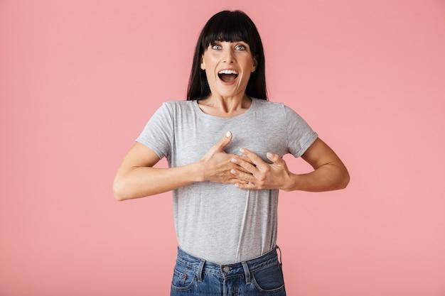 Una bellissima donna eccitata felice incredibile in posa isolata sul muro rosa chiaro.