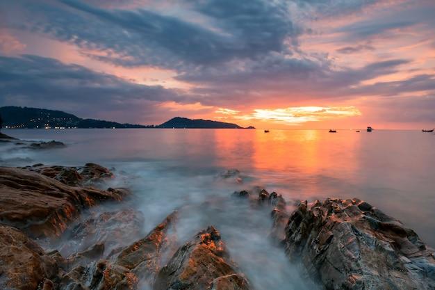 Bella vista sul mare delle andamane al tramonto a kalim patong beach, phuket, thailandia. onda di movimento attraverso la roccia con il cielo twiligh. famosa meta di viaggio per le vacanze estive.