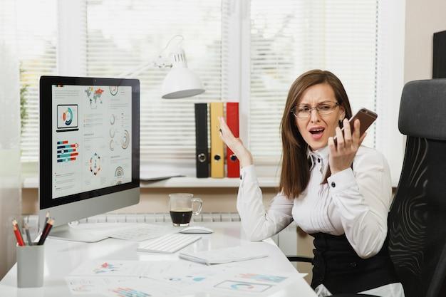 Bella donna d'affari arrabbiata in tuta seduta alla scrivania con una tazza di caffè, lavorando al computer con documenti in ufficio leggero, parlando, imprecando e urlando al telefono cellulare, risolvendo i problemi