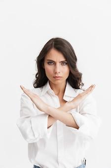 Bella giovane donna arrabbiata con lunghi capelli castani ricci che indossa una camicia bianca in piedi isolata sul muro bianco, mostrando il gesto di arresto