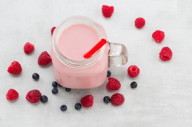 Bellissimo frullato di frutta lamponi rosa antipasto o frullato in barattolo di vetro con sfondo di bacche, vista dall'alto. cocktail allo yogurt. avvicinamento.