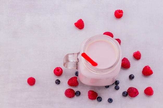 Bellissimo frullato di frutta lamponi rosa antipasto o frappè in vaso di vetro con frutti di bosco