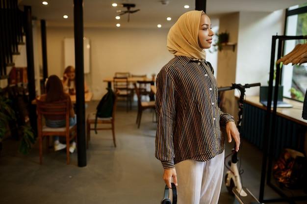 Bella studentessa araba in pose hijab in caffè universitario. donna musulmana con libri seduti in biblioteca.