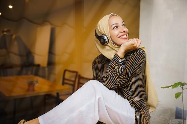 Bella ragazza araba in hijab e cuffie in caffè universitario. donna musulmana con libri seduti in biblioteca.