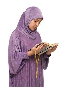 Bella ragazza musulmana araba in abito di moda islamica leggendo il libro sacro del corano, isolato su sfondo bianco