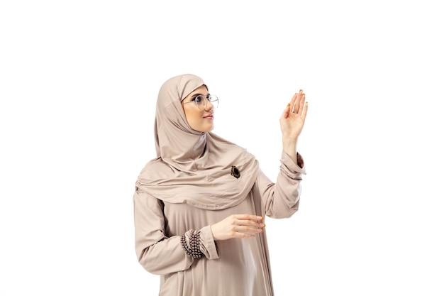 Bella donna araba che posa in hijab alla moda isolato sul concetto di moda del fondo dello studio