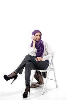 Bella donna araba che posa in abbigliamento elegante dell'ufficio isolato sul concetto di moda del fondo dello studio