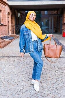 Bella donna araba studentessa musulmana che indossa l'hijab giallo, ritratto femminile alla moda sulla strada della città