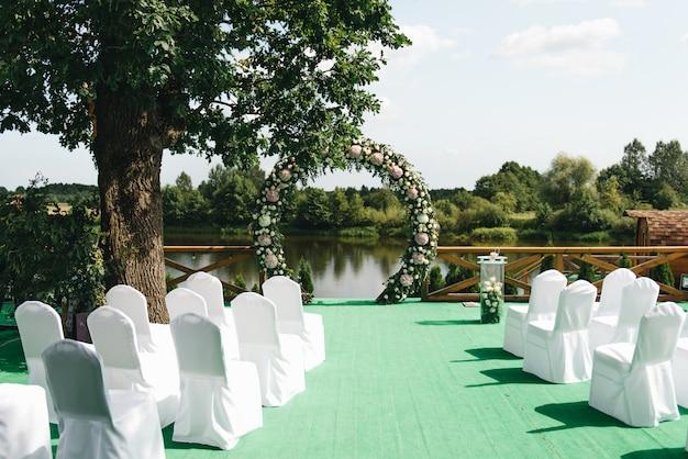 Bello arco per cerimonia di nozze, sfondo naturale degli alberi e del lago, decorazione di nozze
