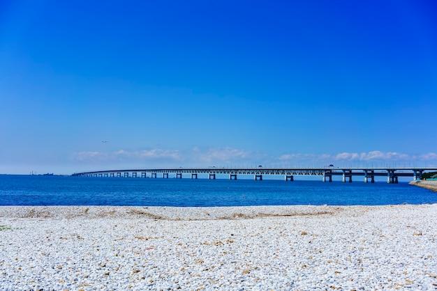 Bellissima spiaggia di marmo artificiale lungo il litorale della città di rinku, con vista kansai kokusai kuko renraku-kyo (strada a pedaggio) attraverso il mare blu della baia di osaka fino all'aeroporto internazionale di kansai, osaka, giappone