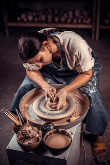 Bella ragazza artigiana che fa ceramiche, scultore di argilla bagnata su ruota.