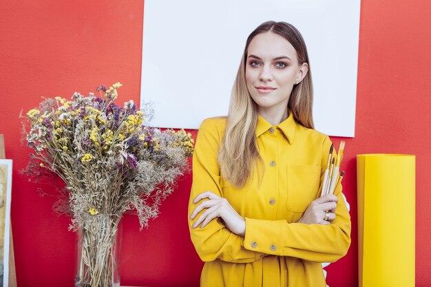 Bellissimo artista. bella giovane artista dagli occhi azzurri che indossa un abito giallo in piedi vicino al muro rosso
