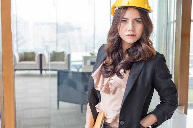 Bella donna di affari dell'asia sopra il fondo blured dell'ufficio.