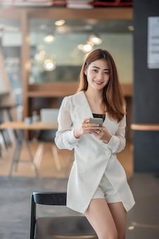Bella donna asiatica di affari che sta usando smartphone in un ufficio moderno.