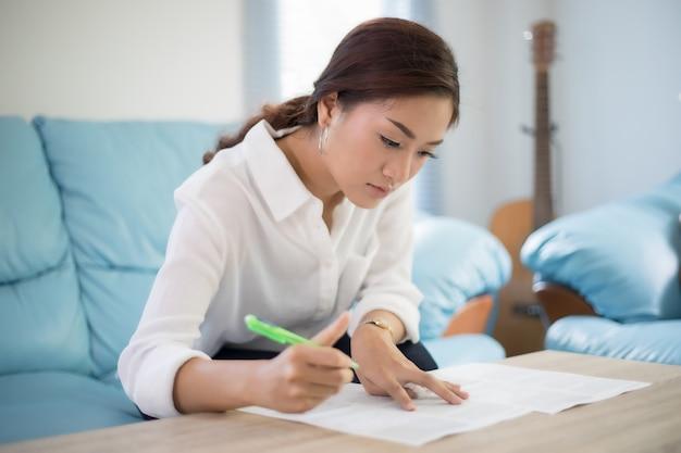 Belle donne asiatiche di affari che scrivono i dati che controllano documento