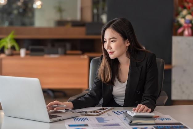 Bella imprenditrice asiatica analizza i grafici utilizzando la calcolatrice portatile in ufficio.