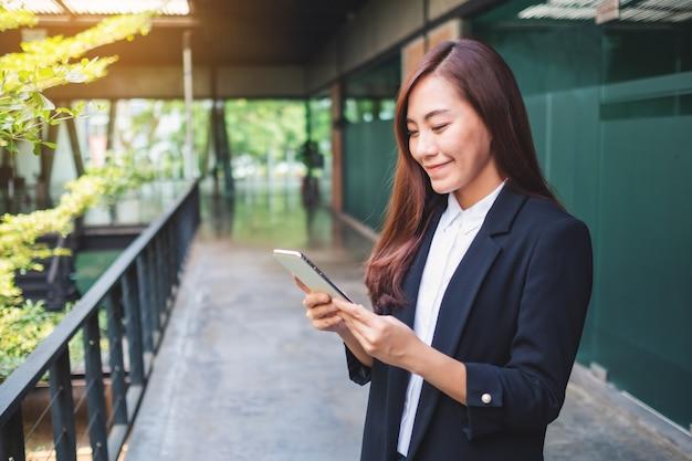 Una bella donna di affari asiatica che tiene e che utilizza telefono cellulare nell'ufficio