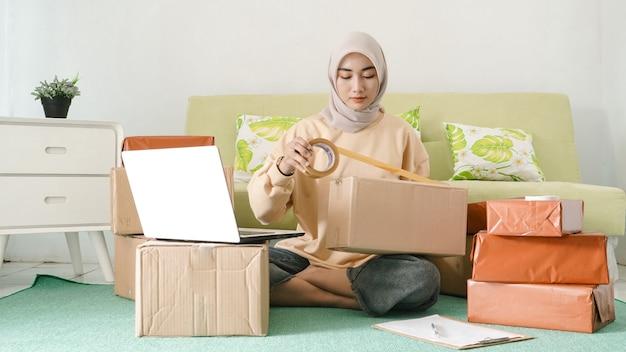 Bella donna d'affari asiatica che imballa gli ordini dei clienti nella sua stanza