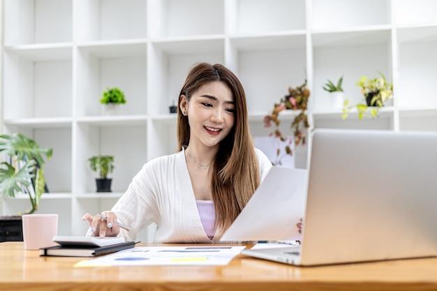 Bella donna d'affari asiatica seduta nel suo ufficio privato, chiacchierando con il suo partner tramite laptop e controllando i documenti, è una dirigente donna di una startup. concetto di gestione finanziaria.