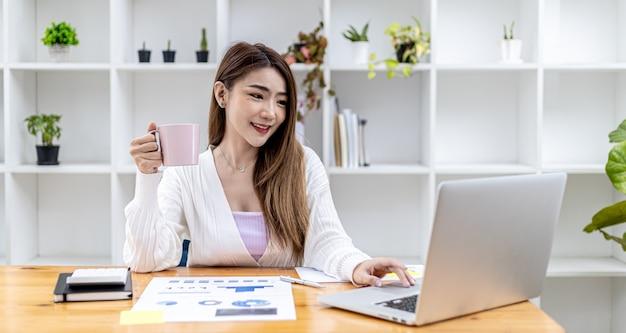 Bella donna d'affari asiatica seduta nel suo ufficio privato, bevendo caffè e guardando le informazioni sul suo laptop, è la dirigente donna di una startup. concetto di gestione finanziaria